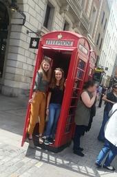 Zwei junge Frauen in einer roten Telefonzelle